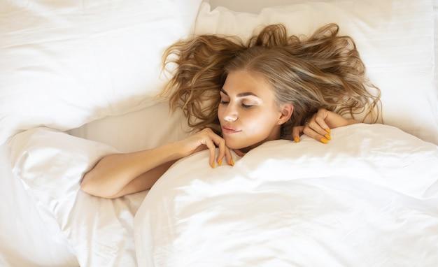 Молодая красивая женщина просыпается в своей постели полностью отдохнувшей. женщина растягивается в постели после пробуждения.