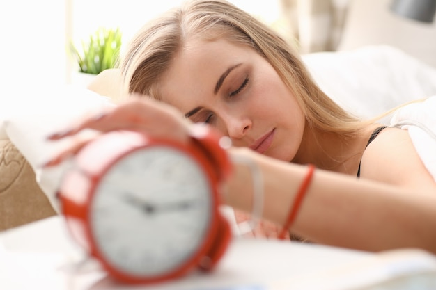 Young beautiful woman waking up in the morning alarm concept