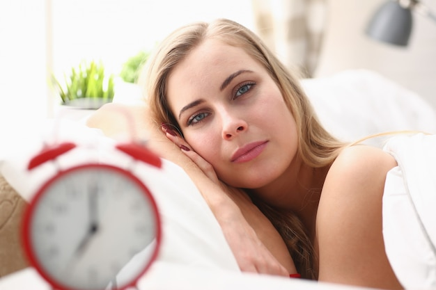 Young beautiful woman waking up in the morning alarm