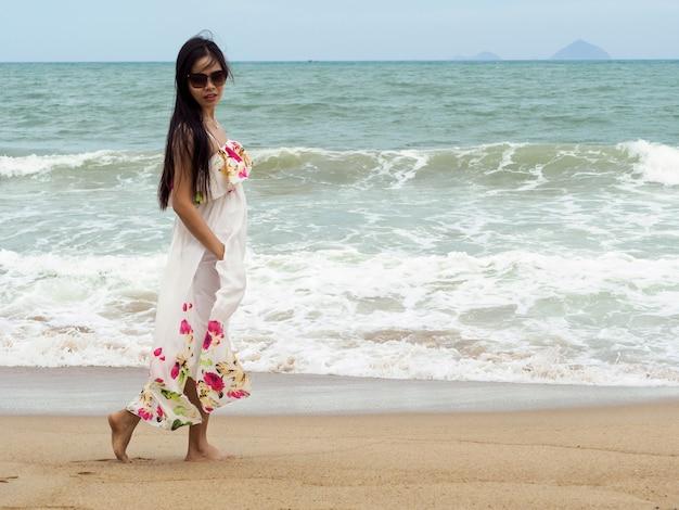 Молодая красивая женщина гуляет по берегу моря и смотрит на море. летнее время, путешествия, туризм, отдых или концепция отпуска
