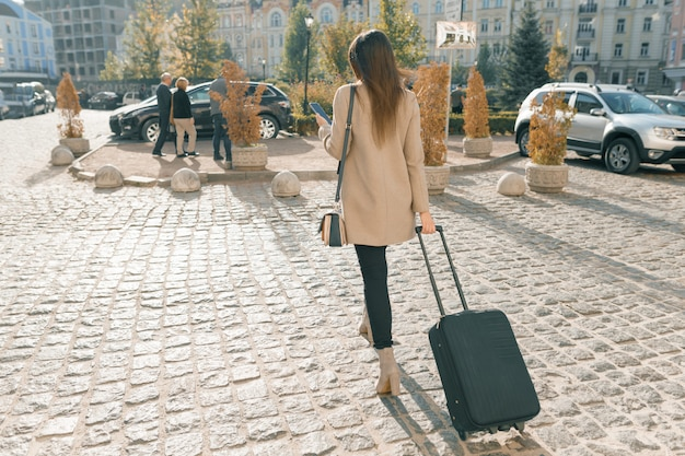 Young beautiful woman walking along city street with travel suitcase