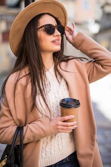 ハンドバッグと一杯のコーヒーが付いている通りに沿って歩く若い美しい女性。