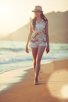Молодая красивая женщина идет босиком вдоль прибоя на песчаном пляже на закате