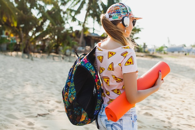 Giovane bella donna che cammina sulla spiaggia che tiene materassino yoga, stile malloppo sportivo hipster, pantaloncini di jeans, t-shirt, zaino, soleggiato, fine settimana estivo