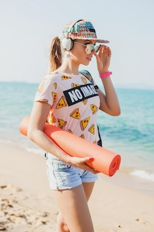 Young beautiful woman walking on beach with yoga mat, listening to music on headphones, hipster sport swag style, denim shorts, t-shirt, backpack, cap, sunglasses, sunny, summer weekend, cheerful