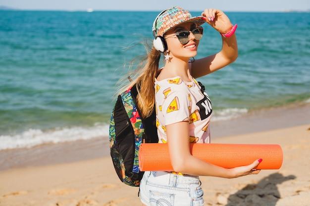 Giovane bella donna che cammina sulla spiaggia con materassino yoga, ascoltando musica in cuffia, stile malloppo sportivo hipster, pantaloncini di jeans, t-shirt, zaino, berretto, occhiali da sole, soleggiato, weekend estivo, allegro