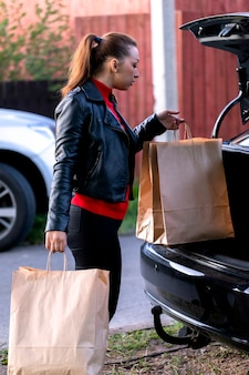 Young beautiful woman walking to car with purchases from supermarket
