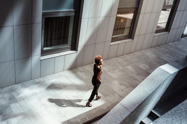 Young beautiful woman walking down city
