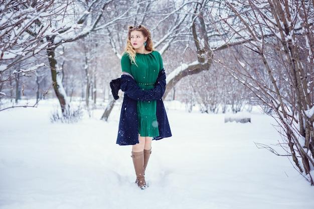 公園を歩いて、新鮮な冬の空気を呼吸し、素晴らしい気分の若い美しい女性。モデルプラスサイズ