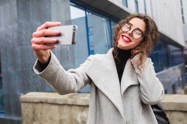 グレーのコート、秋のファッションスタイル、メガネ、スマートフォンを保持している、selfie写真を撮る、笑顔、幸せで街を歩く若い美しい女性