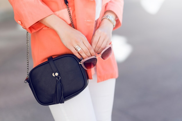トレンディなカジュアルグラマー服、ピンクのジャケットで旧市街を歩く若い美しい女性。春または秋のシーズン、晴天。詳細。