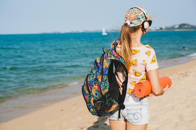 ヨガマット、流行に敏感なスポーツ盗品スタイル、デニムのショートパンツ、tシャツ、バックパック、晴れ、夏の週末を保持してビーチを歩く若い美しい女性