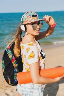 ヨガマットとビーチを歩いて、ヘッドフォンで音楽を聴いて、流行に敏感なスポーツ盗品スタイル、デニムのショートパンツ、tシャツ、バックパック、キャップ、サングラス、晴れ、夏の週末、陽気な若い美しい女性