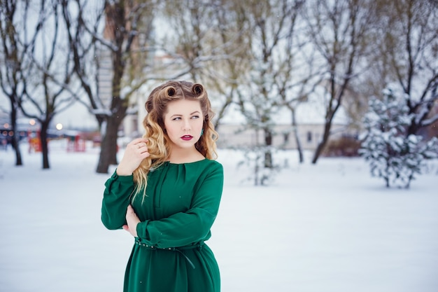 Young beautiful woman walking in a park and breathing fresh winter air and feeling wonderful. model plus size