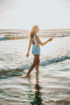 A young beautiful woman walking on the seaside during daytime