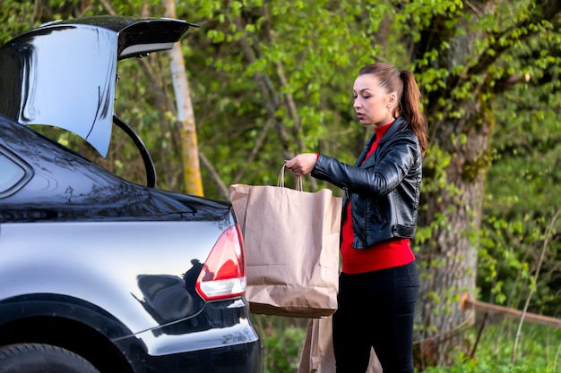 Молодая красивая женщина идет к машине с покупками в супермаркете