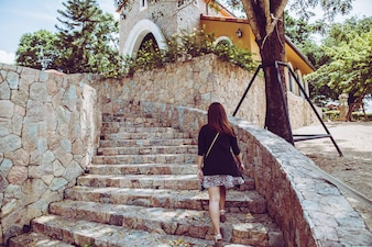Young beautiful woman walking up the stone stairs with natural background. Step for success concept.