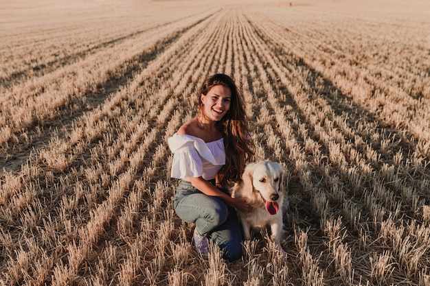 Young beautiful woman walking with her golden retriever dog on a yellow field at sunset