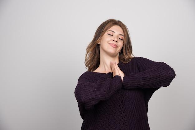 Giovane bella donna in caldo maglione lavorato a maglia in piedi su un muro grigio.