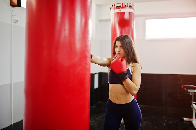 Young beautiful woman, wear on boxing gloves doing exercises and working hard in gym