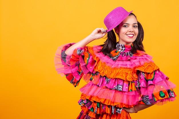 スタジオで黄色の背景の上にマスカレードラテン系の衣装を着ている若い美しい女性