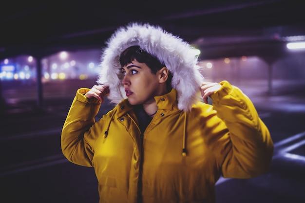 ぼやけた街で夜に黄色の冬のコートを着ている若い美しい女性