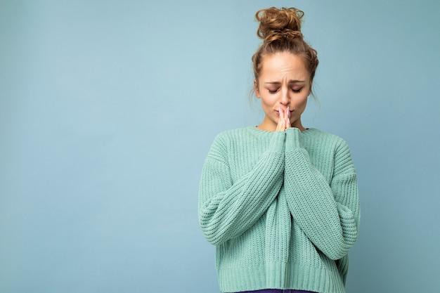 Молодая красивая женщина в повседневном синем свитере и молится, взявшись за руки вместе