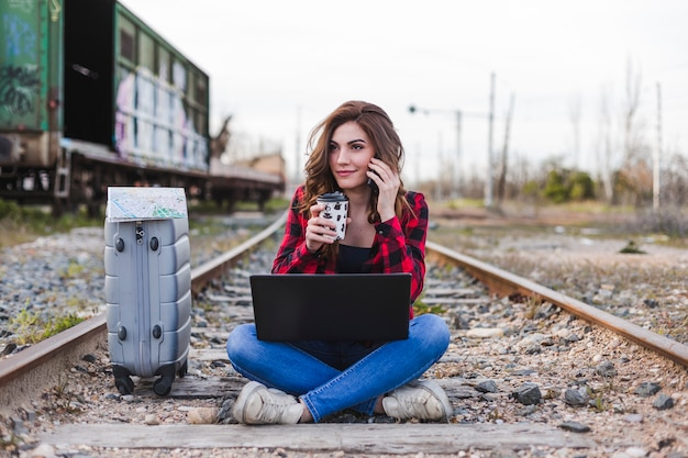 Young beautiful woman wearing casual clothes, sitting on the railway with suitcase, laptop and talking on her mobile phone., she is smiling and holding a cup of coffee. outdoors lifestyle. travel