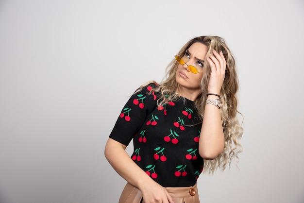 Молодая красивая женщина в повседневной футболке, глядя далеко с рукой над головой.