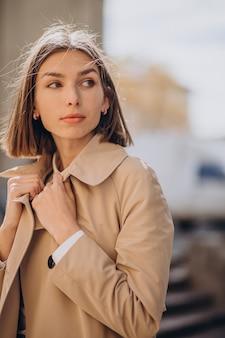 Cappotto da portare della giovane bella donna che cammina nella città