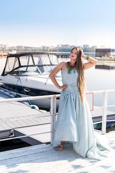 Молодая красивая женщина в платье и позирует с яхтой