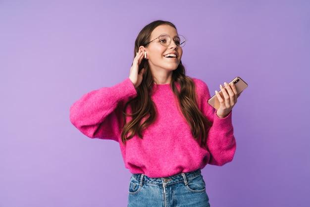 이어폰을 끼고 웃고 핸드폰을 들고 있는 아름다운 젊은 여성