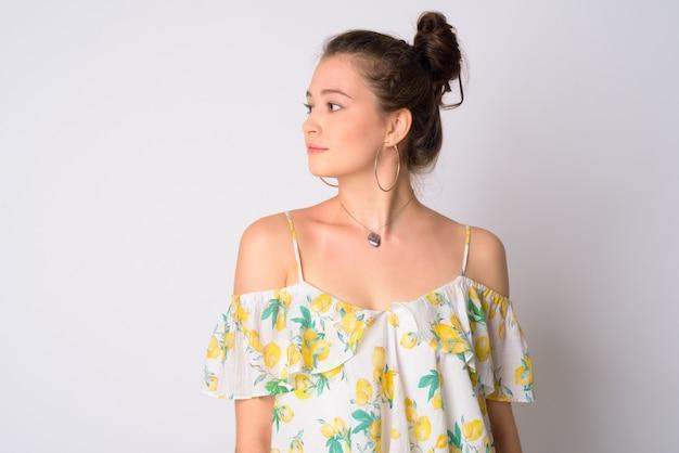 花のオフショルダードレスを着ている若い美しい女性