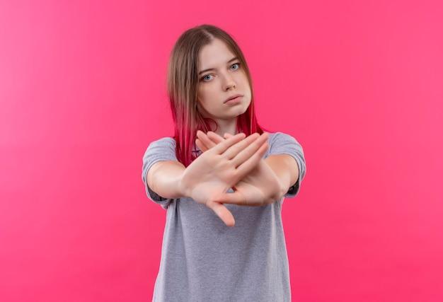 격리 된 분홍색 벽에 중지 제스처를 보여주는 회색 티셔츠를 입고 젊은 아름 다운 여자
