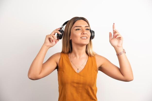 白い背景の上にヘッドフォンを身に着けている若い美しい女性。