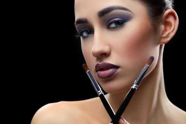 Young beautiful woman wearing professional makeup holding makeup
