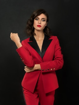 黒の上にポーズをとって赤いファッションスーツを着て若い美しい女性