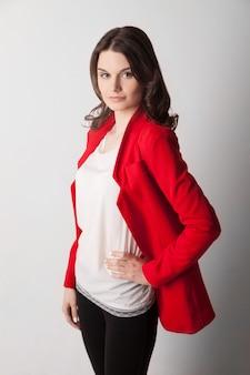 스튜디오에서 포즈를 취하는 빨간 재킷을 입은 젊은 아름다운 여성