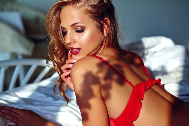 朝ベッドに赤いランジェリーを着ている若い美しい女性