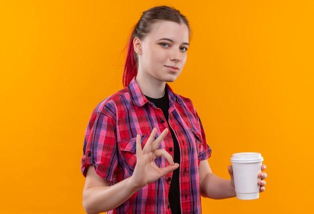 孤立した黄色の壁に大丈夫なジェスチャーを示すコーヒーのカップを保持している赤いシャツを着て若い美しい女性