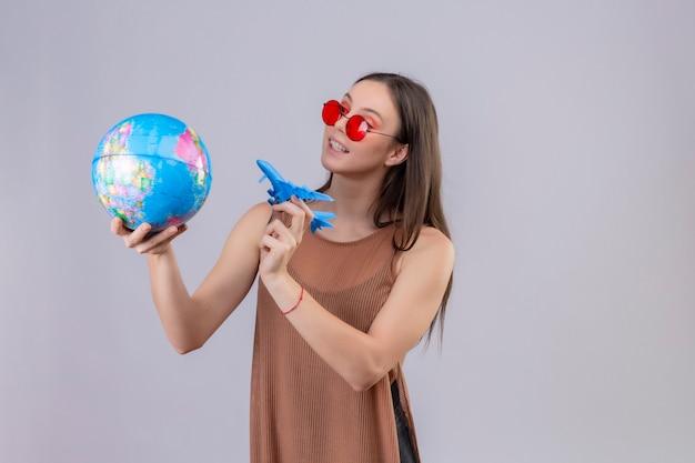 Молодая красивая женщина в красных солнцезащитных очках держит глобус и игрушечный самолетик, игривое и счастливое положение на белом фоне