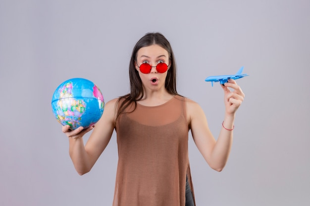 Young beautiful woman wearing red sunglasses holding globe and toy airplane amazed and surprised over white wall