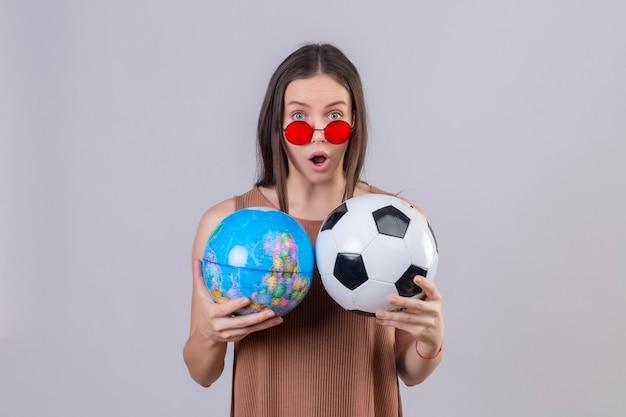 Молодая красивая женщина в красных темных очках держит футбольный мяч и глобус удивлен и удивлен над белой стеной