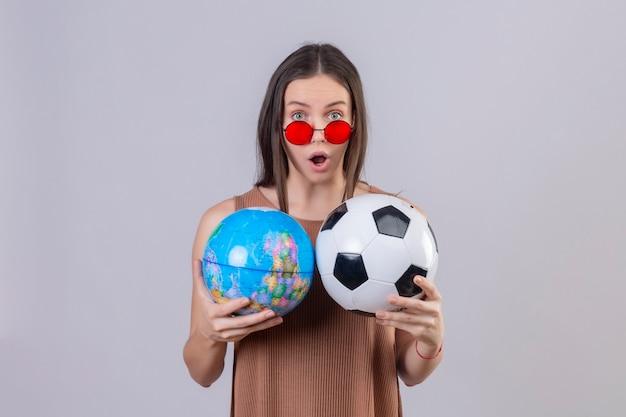 Молодая красивая женщина в красных солнцезащитных очках, держащая футбольный мяч и глобус, поражена и удивлена, стоя на белом фоне