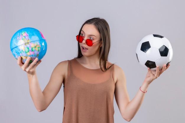 Молодая красивая женщина в красных солнцезащитных очках держит футбольный мяч и глобус, глядя на него с удивлением, стоя на белом фоне