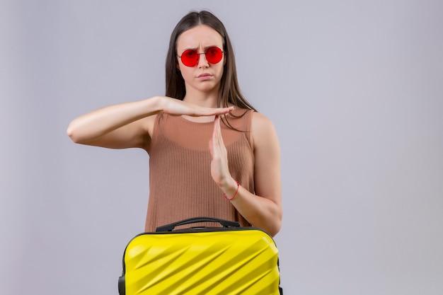 Молодая красивая женщина в красных солнцезащитных очках стоит с дорожным чемоданом и выглядит усталой, недовольной, делая жест тайм-аута с руками, стоящими на розовом фоне