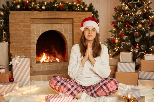 Молодая красивая женщина в шляпе санты на фоне елки и камина, прося и молясь руками вместе, с выражением надежды на лице, очень спокойно, смотрит в камеру.