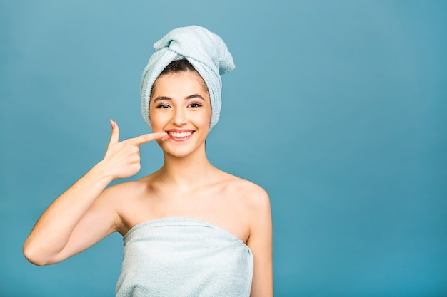 Young beautiful woman wearing shower towel after bath standing over isolated blue background Premium Photo