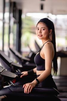 운동복, 땀 방지 직물 및 러닝 머신에 서있는 스마트 워치를 입고 젊은 아름다운 여자가 현대 체육관에서 운동하기 전에 워밍업