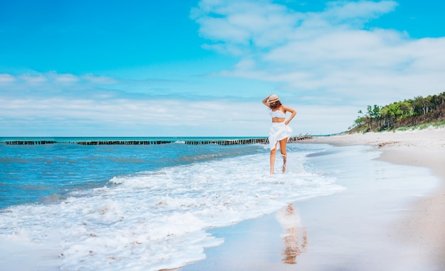 Young beautiful woman wearing straw hat and white swimsuit and skirt posing running along the surf line on beach near waves.